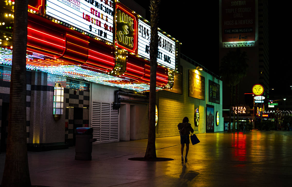 A woman walks away from the Fremont Street Experience following Gov. Steve Sisolak's statewide ...