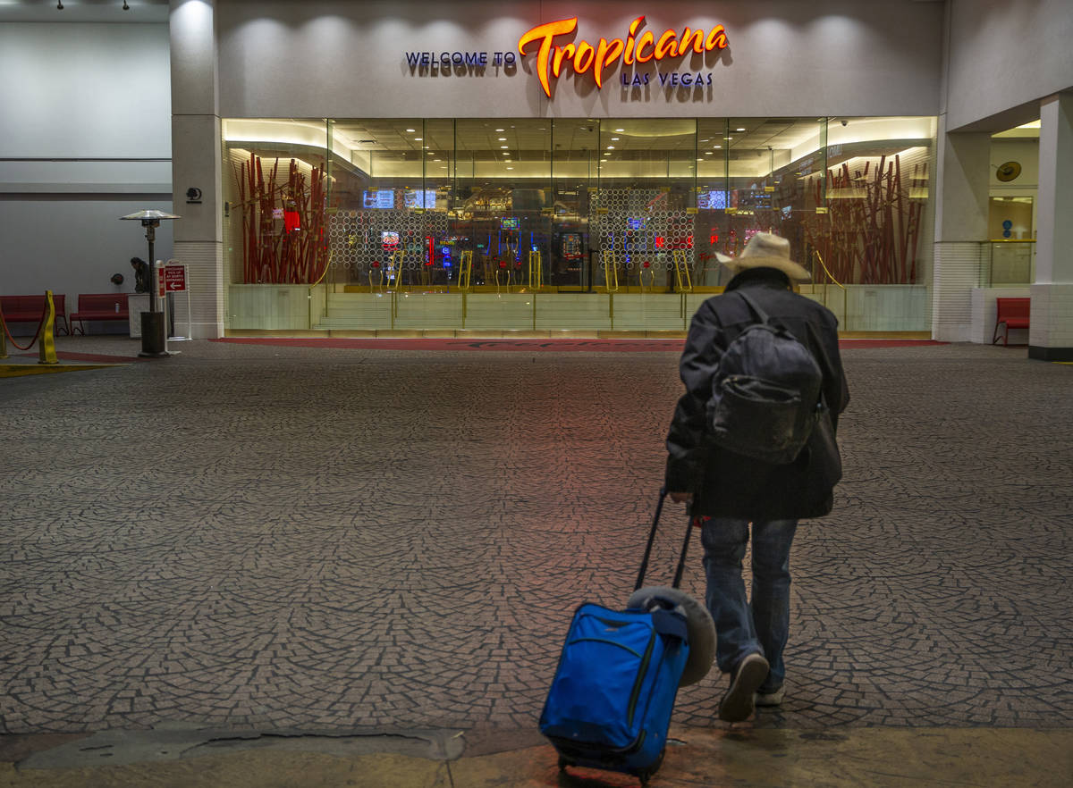 A lone traveler walks towards the entrance to the Tropicana as non-essential business closures ...