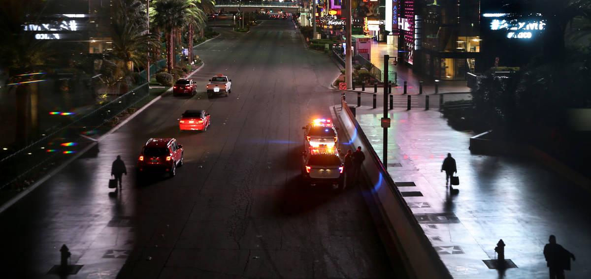 A few pedestrians walk along Las Vegas Blvd. near the MGM Grand as non-essential business closu ...