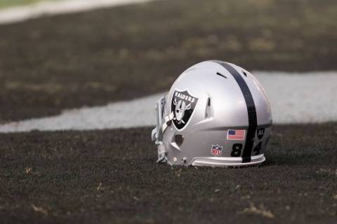 An Oakland Raiders helmet sits on the Oakland-Alameda County Coliseum field before the game aga ...