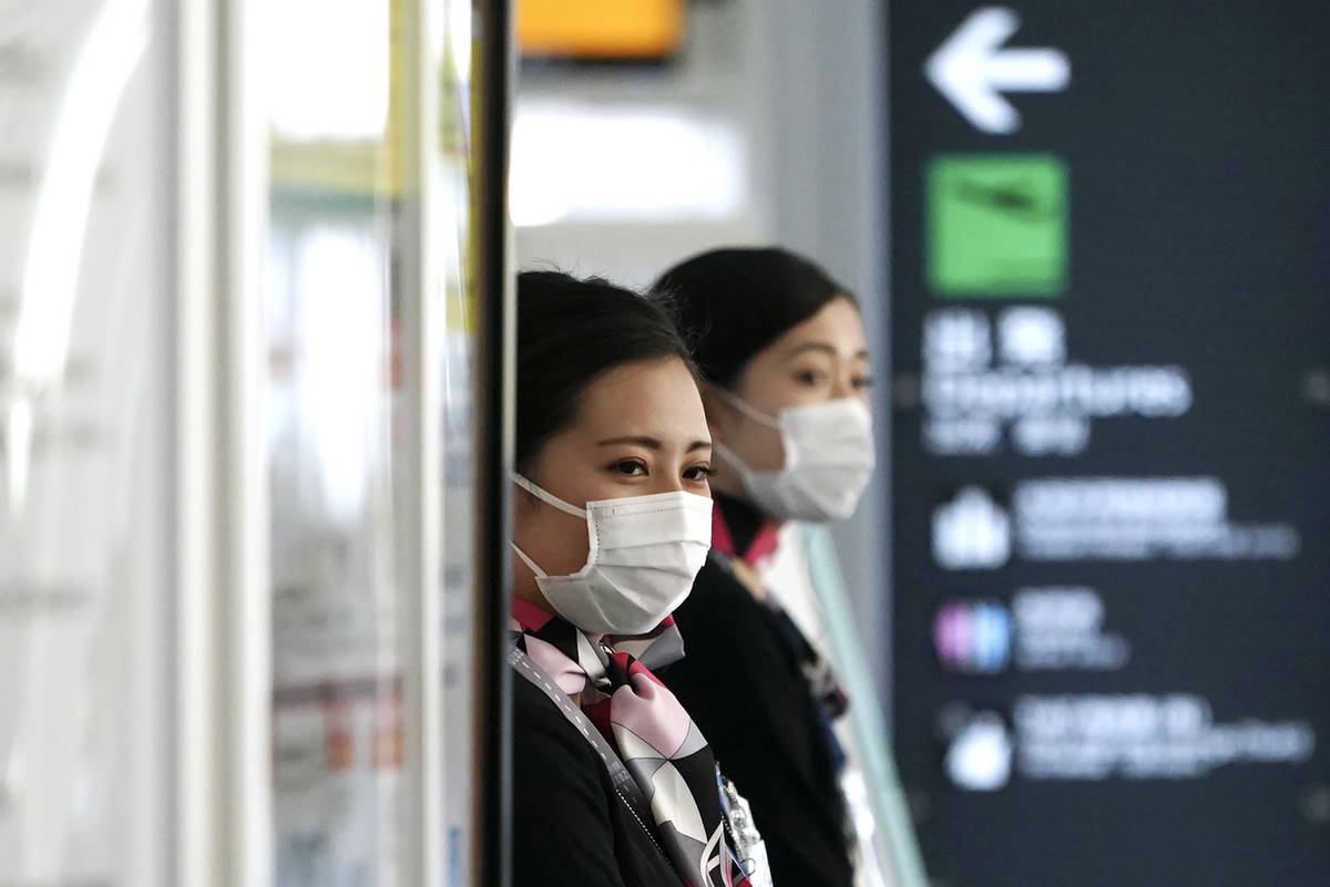 Airlines ground crews with protective masks to protect against the coronavirus stand at a check ...