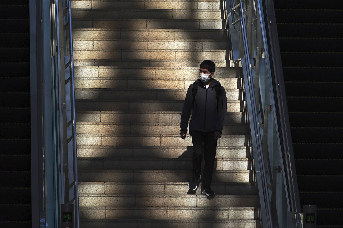 A man with a mask to protect against the coronavirus walks down a flight of stairs at the Haned ...