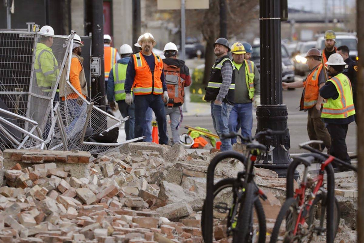 Construction workers looks at the rubble from a building after an earthquake Wednesday, March 1 ...