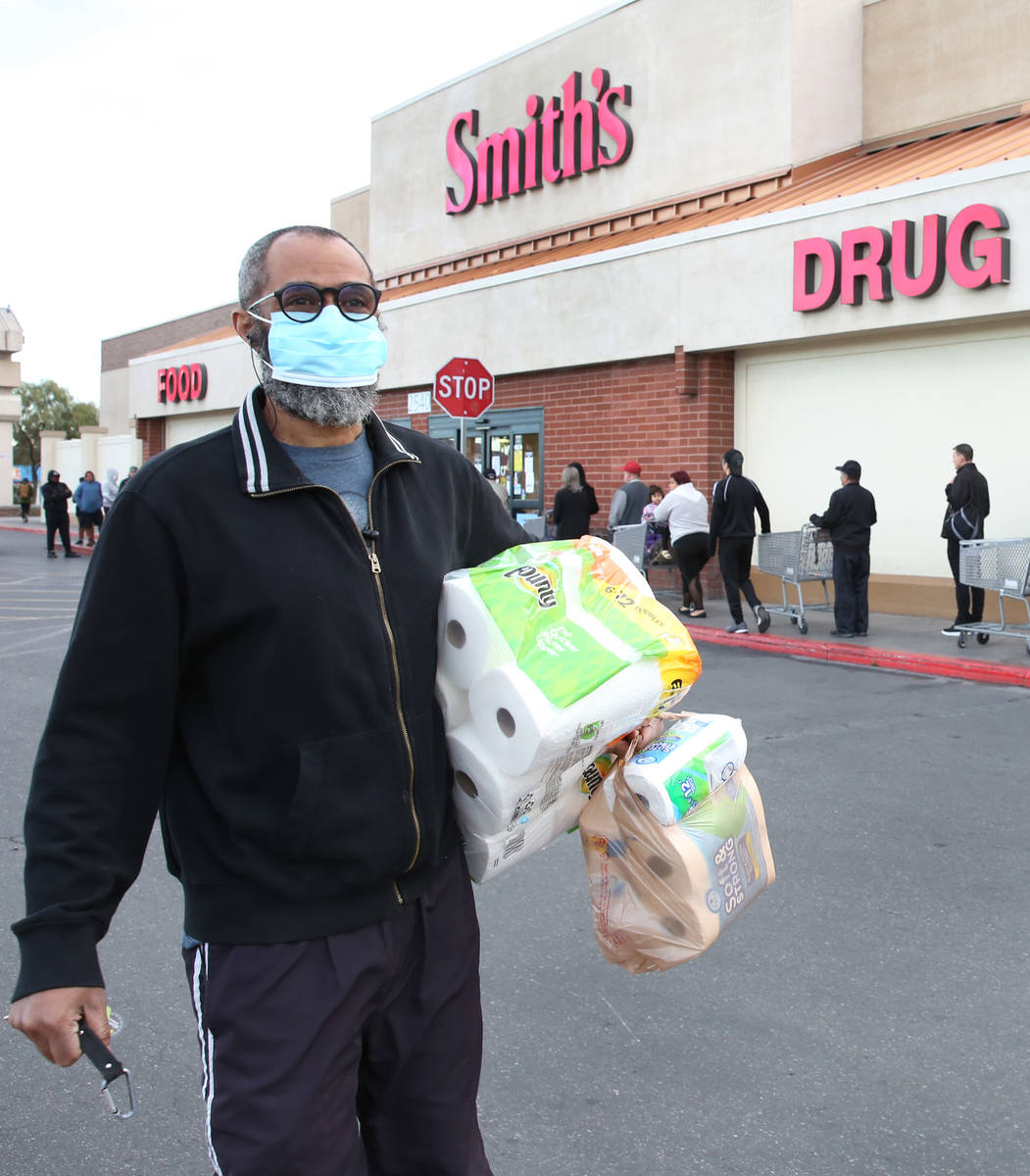 Terrance Brown carries toilet papers after shopping at a Smith's store on Maryland Parkway on W ...