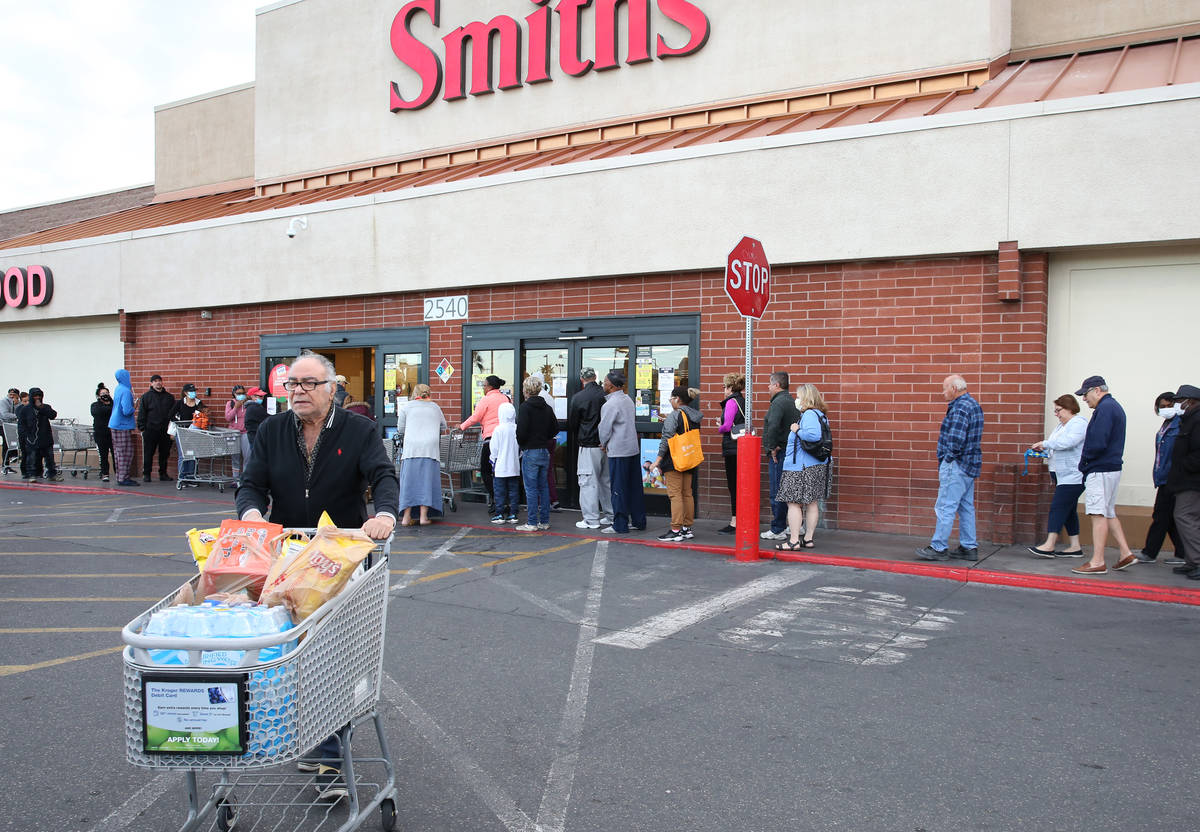 Jim Nazemi, 81, pushes his shopping cart after shopping as other seniors line up at a Smith's s ...