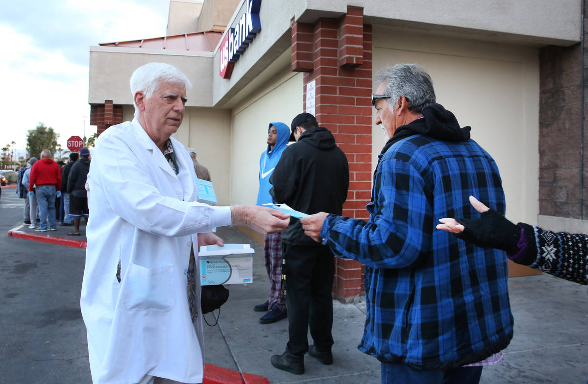 Dr. Mike Moore handouts face mask to seniors who lined up outside a Smith's store on Maryland P ...