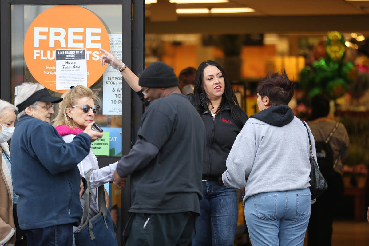 Smith's store manager Jessica Iverson assists seniors over 60 who were allowed into the grocer ...
