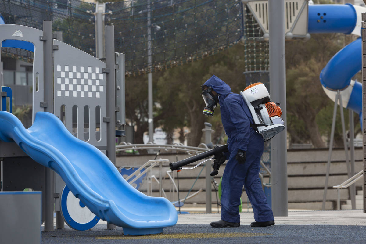 A worker sprays disinfectant as a precaution against the coronavirus at a playground in the cen ...