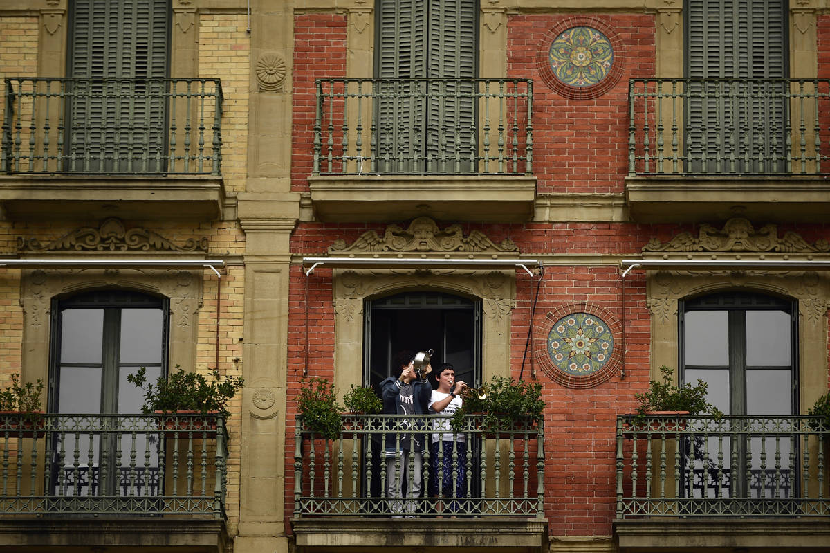 A young boy plays his trumpet from a balcony, in Pamplona, northern Spain, Wednesday, March 18, ...