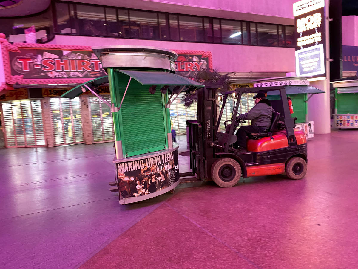 A worker removes kiosks at Fremont Street Experience in downtown Las Vegas Wednesday, March 18, ...