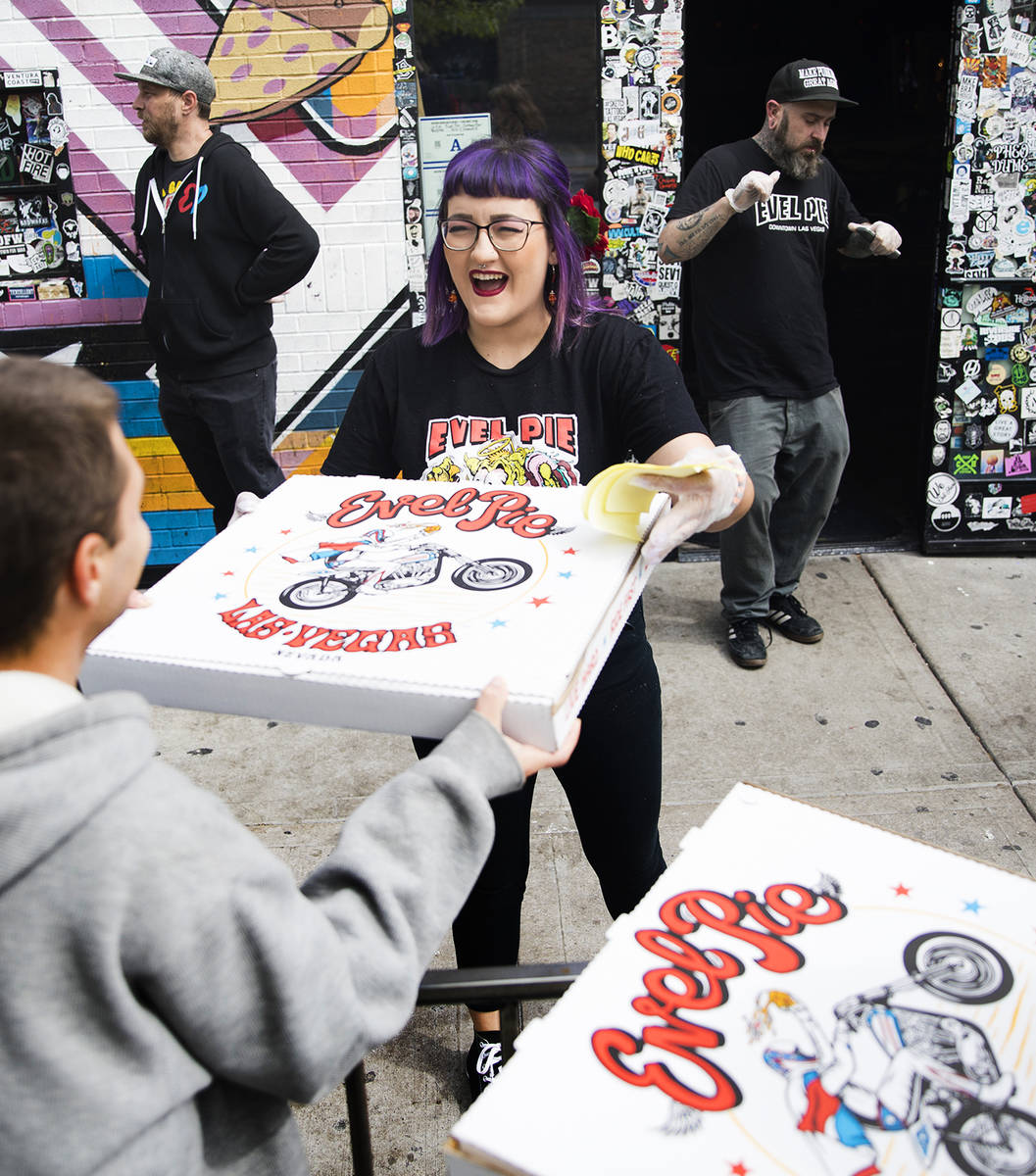 Employee Aly Bosnos hands out a pizza at Evel Pie in Las Vegas, Wednesday, March 18, 2020. Evel ...