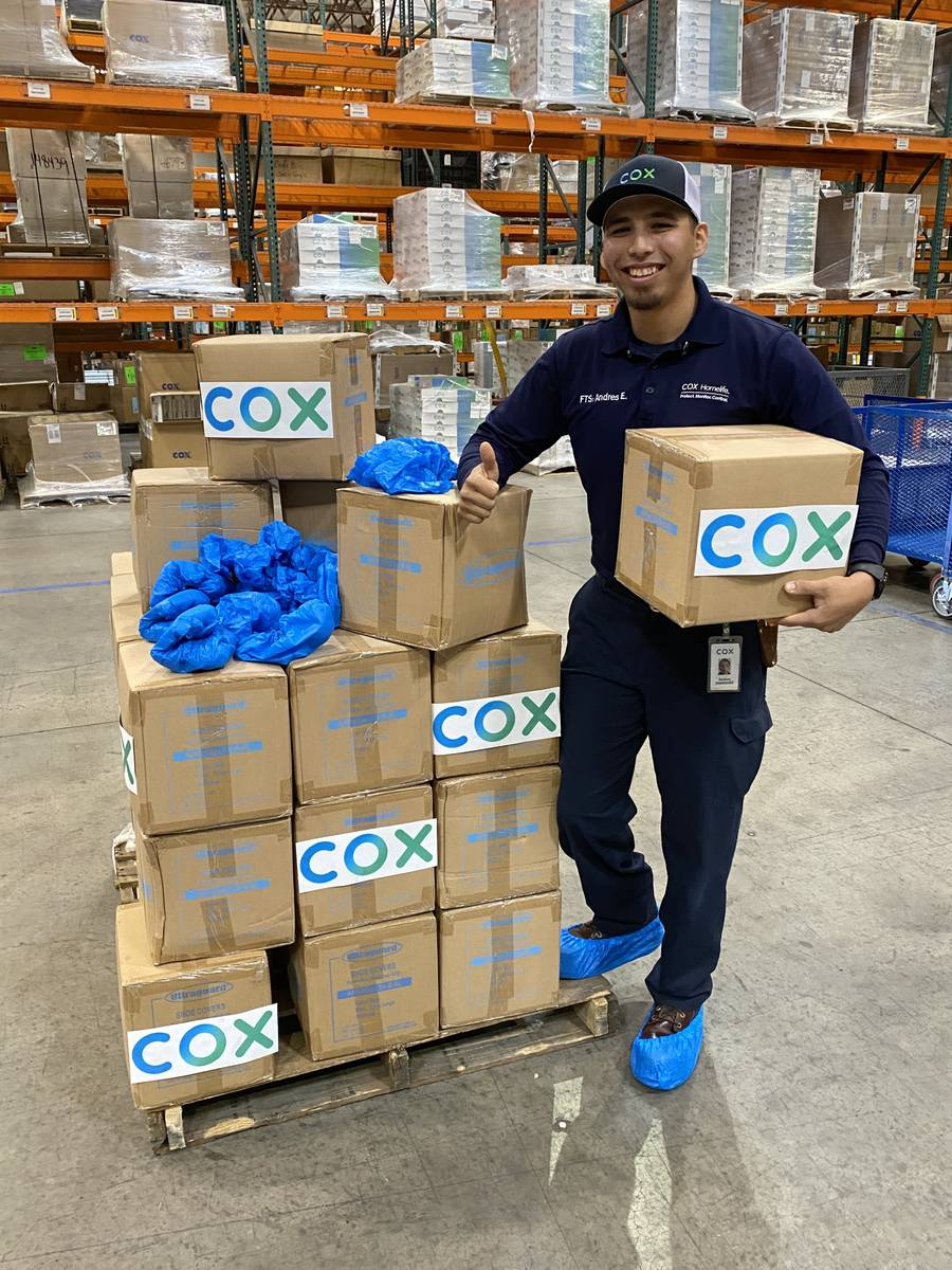 Cox Field Technician Andres Enriquez prepares boxes of protective shoe covers for UMC in one of ...