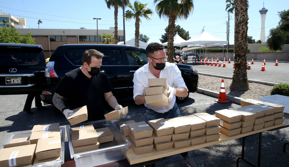 Brian Howard, left, and John Anthony, co-owners of Sparrow + Wolf restaurant, deliver food to p ...