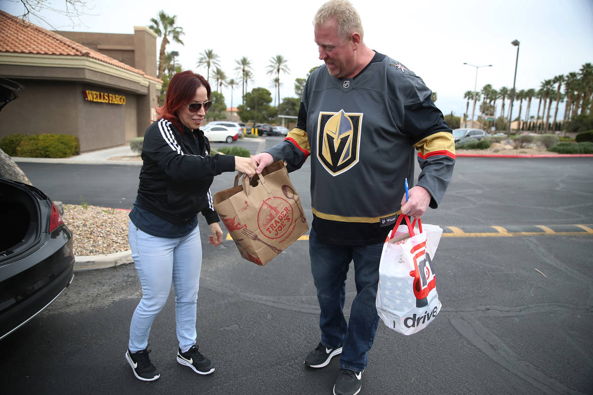 Brenda Karcz, left, makes a donation to Matty Evans who was collecting paper goods, cleaning su ...