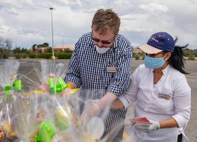 Volunteer Gary Perkins, left, and Demi Hou, owner and operator of Demi's Gift Baskets, add groc ...