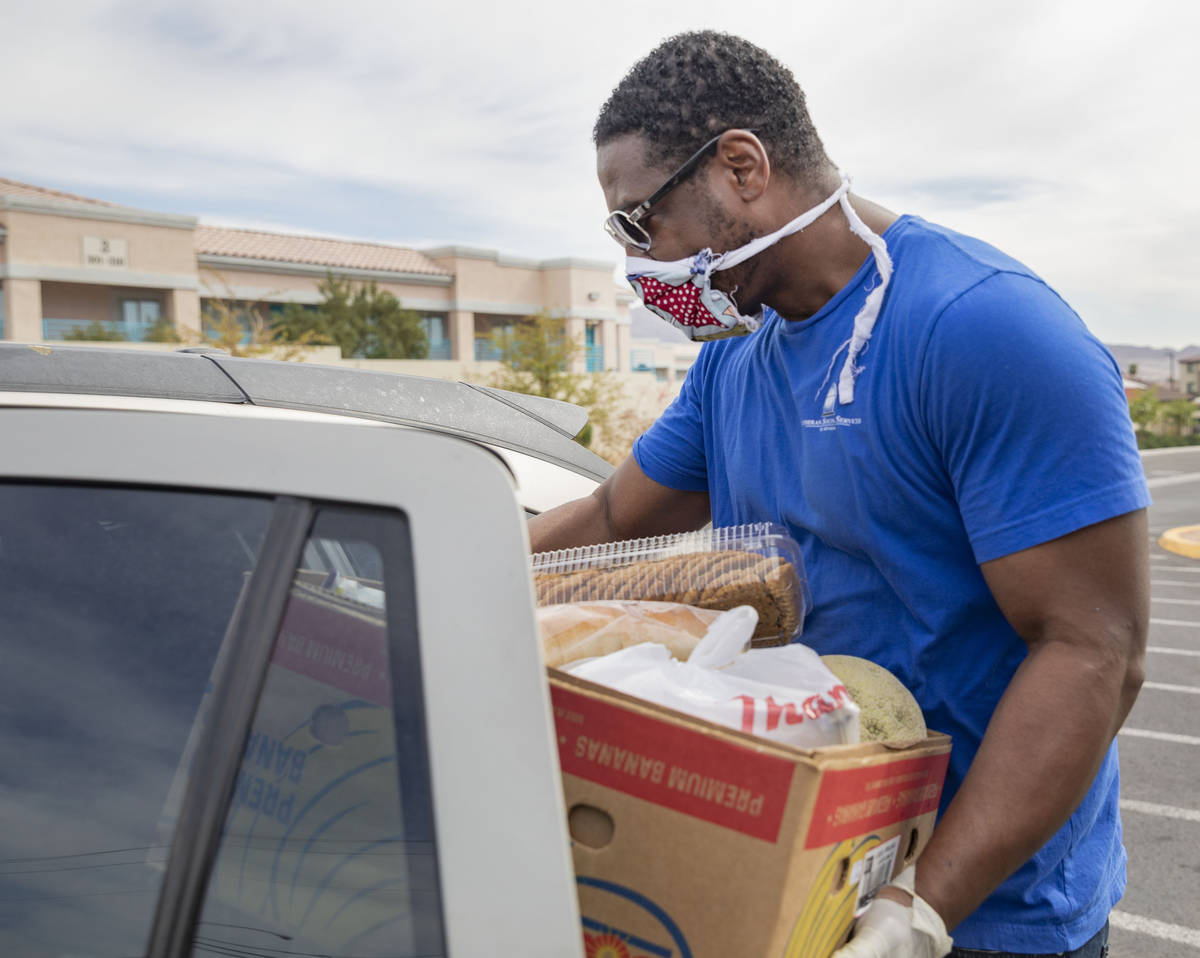 Case manager for Lutheran Social Services of Nevada Raymond Watkins loads a vehicle with an eme ...