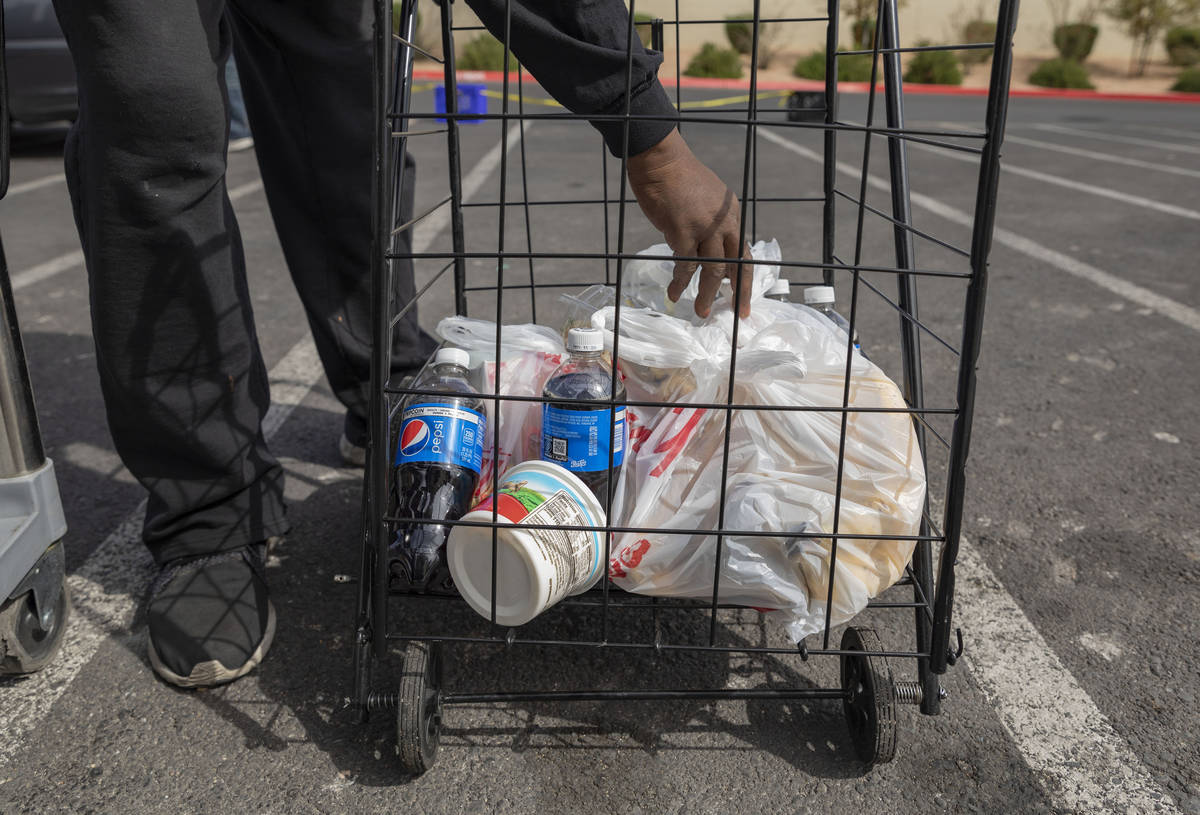 An individual loads a cart with an emergency food kit at Lutheran Social Services of Nevada, in ...
