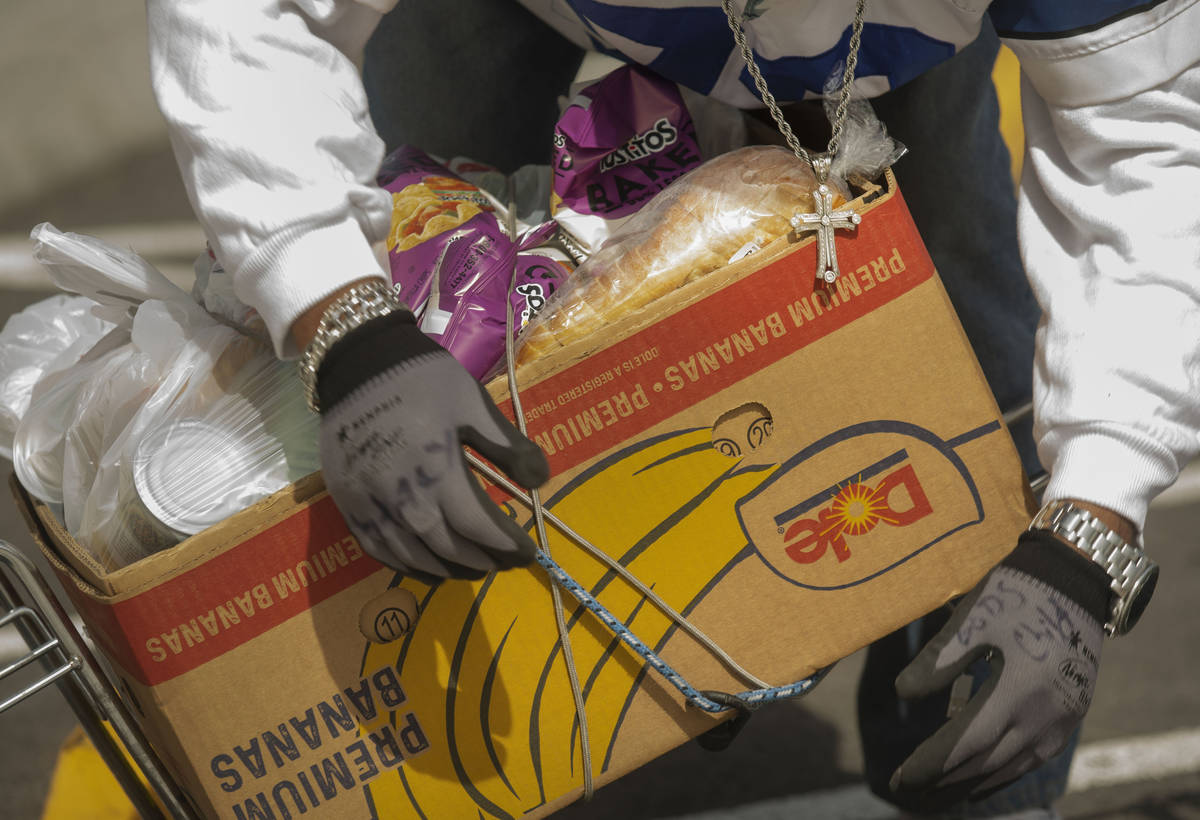 An individual straps an emergency food box to his bike at Lutheran Social Services of Nevada, i ...