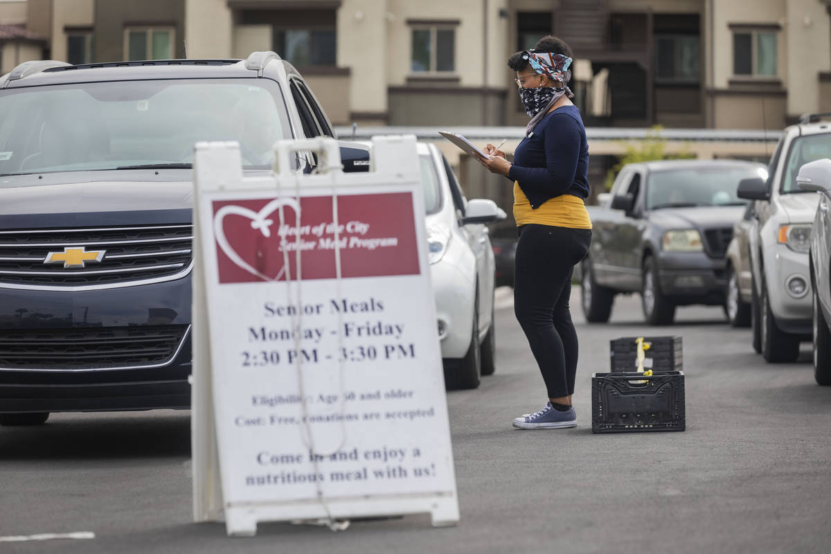 Community health worker for Lutheran Social Services of Nevada A.J. Tullos, greet a vehicle in ...