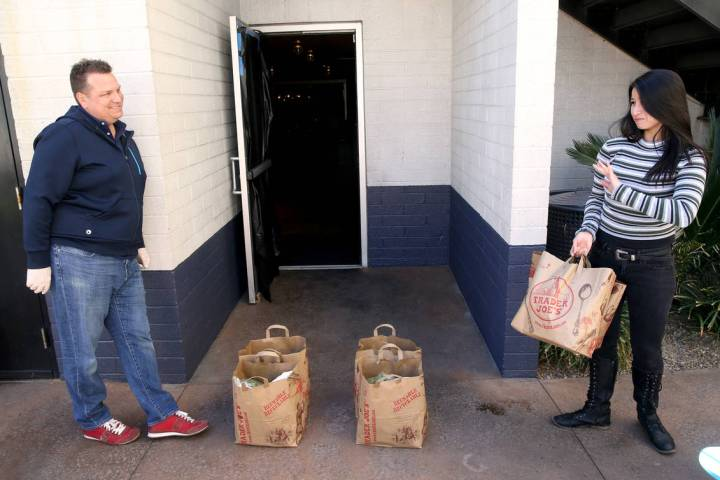 Laid off Carson Kitchen server Anjel Moore receives food packages at a safe distance from owner ...