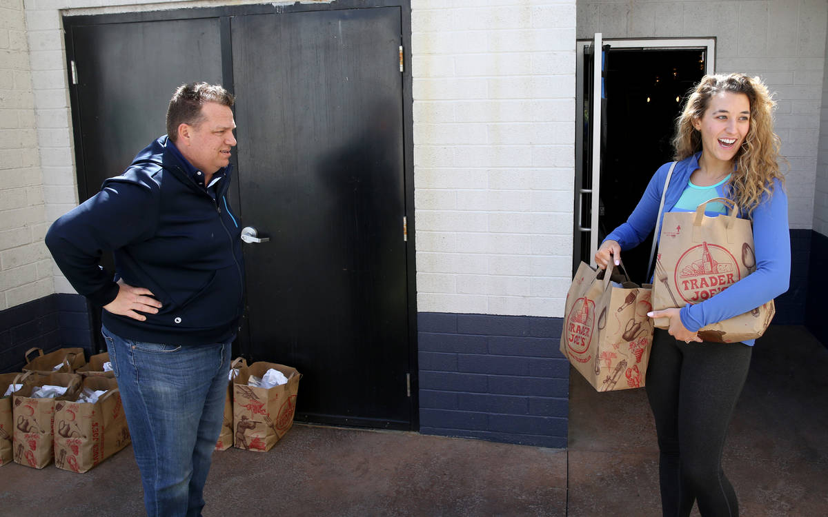 Laid off Carson Kitchen bartender Sarah Drummer receives food packages at a safe distance from ...