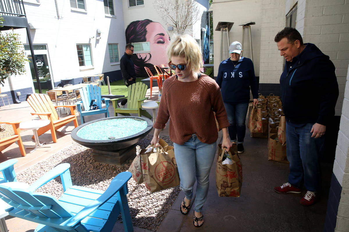 Laid off Carson Kitchen bartender Felicia Taylor, left, receives food packages from manager Rac ...