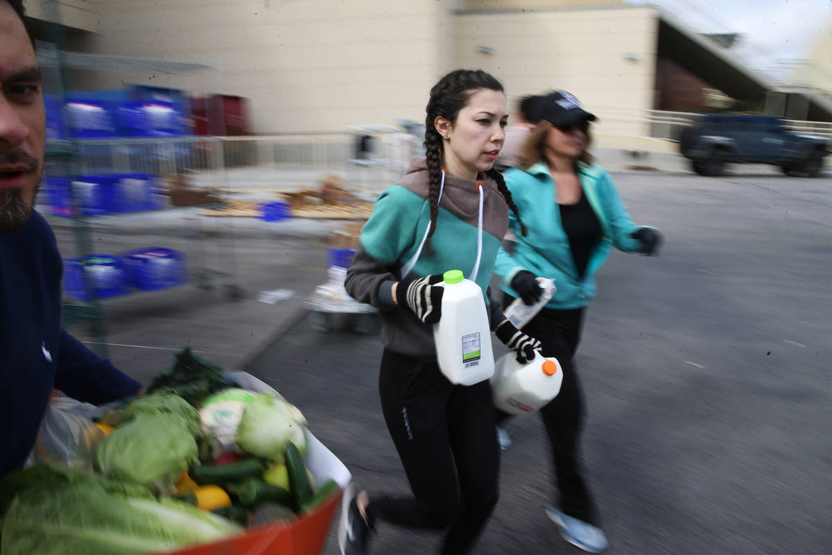 Assistant food and beverage manager Luisa Difalco, center, sprints to car to hand out milk to a ...