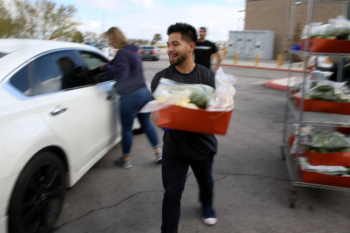 Food and beverage manager Anthony Tugaoen delivers food to a team member's car at the M Resort ...