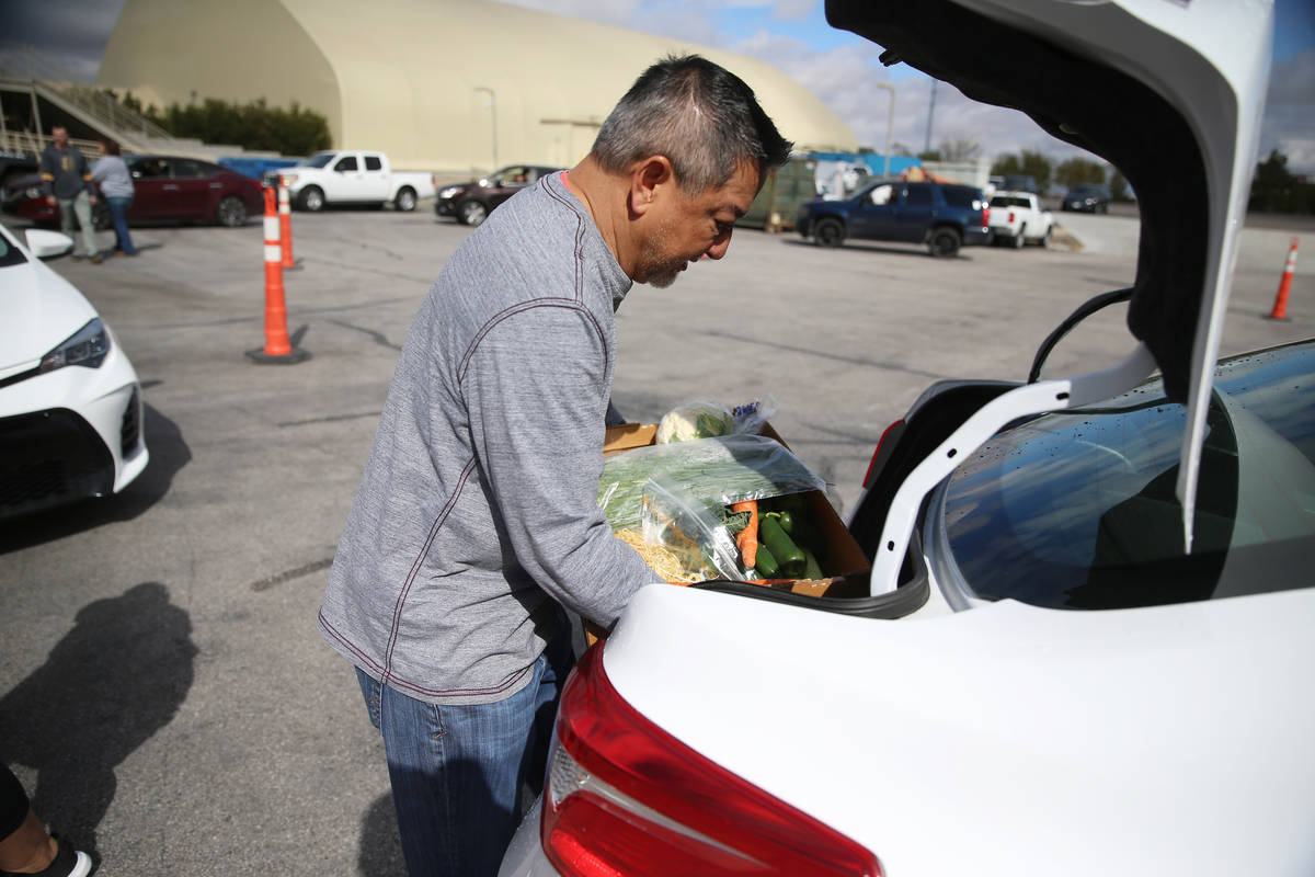 Executive director of player services Luke McEwin delivers food to a team member's car at the M ...