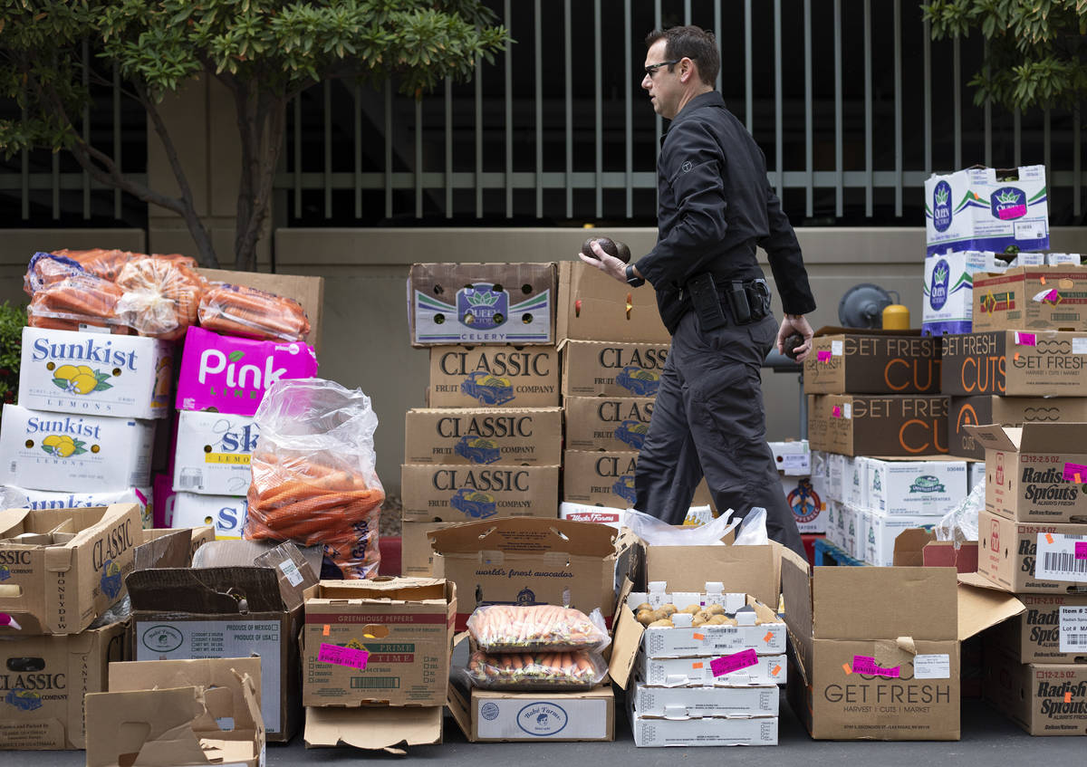 A police officer moves avocados as a food donation is staged at the Las Vegas Metropolitan Poli ...