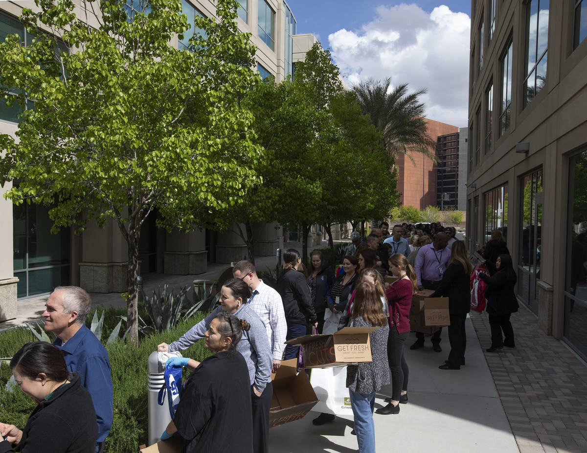 Hundreds line up outside the Las Vegas Metropolitan Police Department headquarters to get produ ...