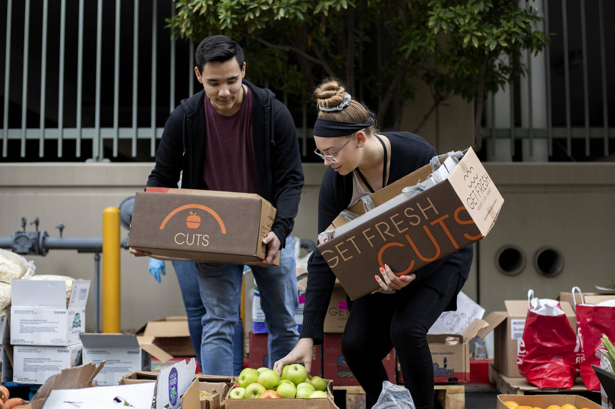 Chris Hernandez, left, and Ashlyn Haman, right, pick out produce at a food donation outside the ...