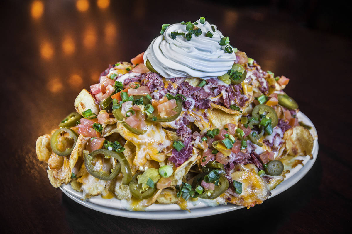 McMullan's Irish nachos with shredded corn beef, homemade potato chips, layered cheddar cheese, ...