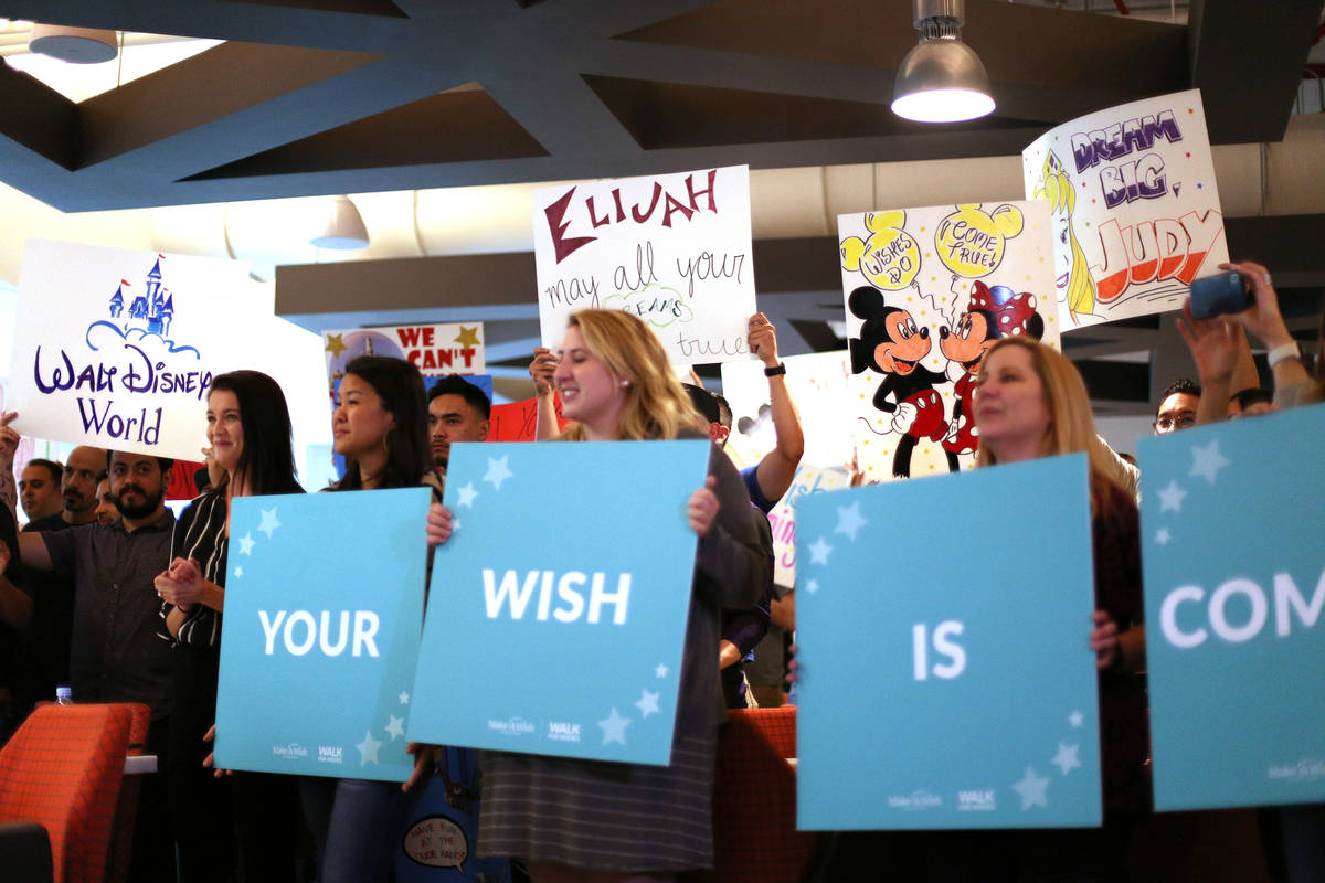 UFC employees hold up signs of wishes for children at an event by Make-A-Wish in partnership wi ...