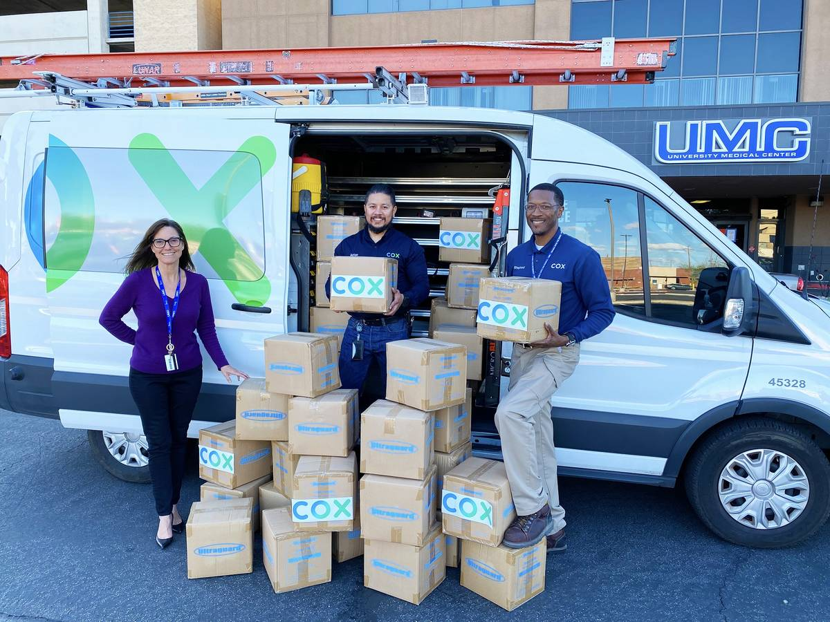 Cox Communications' Field Technicians Adrian Alcala and Rodney Shepherd donate protective shoe ...