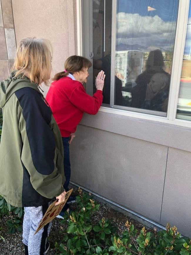 Judy and Jan Swanson visit their family member, Mel Swanson, outside his window at his assisted ...
