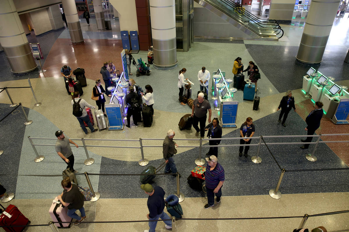Passengers check in for flights at American Airlines at McCarran International Airport in Las V ...
