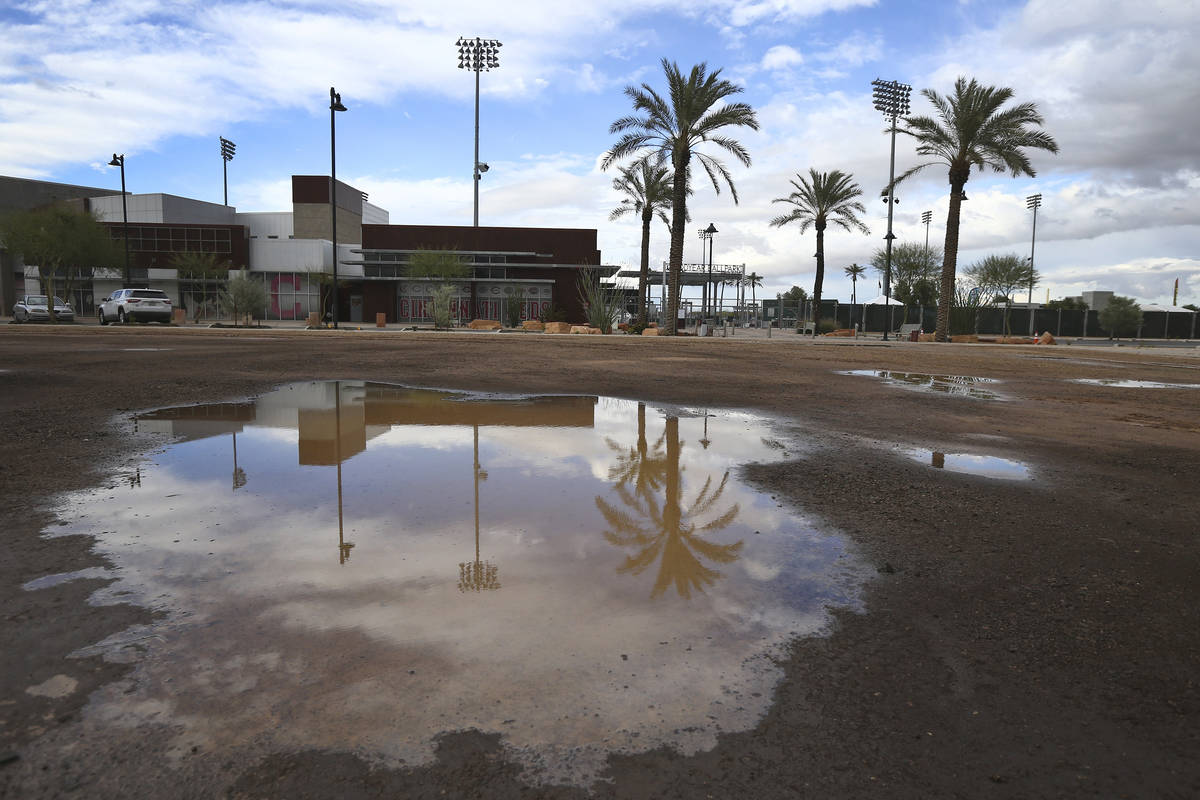 A puddle in an empty parking lot reflects a closed Goodyear Ballpark, home of the Cleveland Ind ...