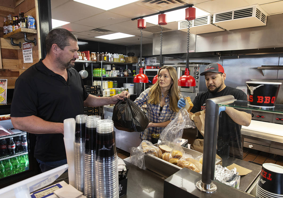 Brian Buechner, left, and wife Natalia Badzjo, owners of Big B's Texas BBQ, prepare an order wi ...