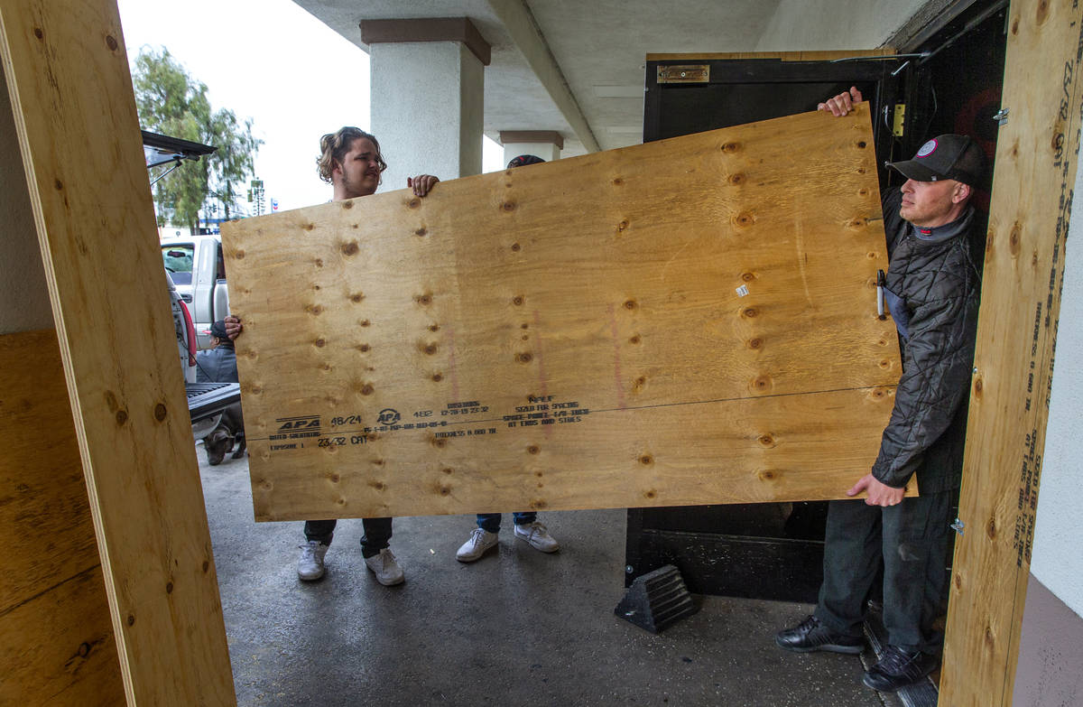 Cooper Cooley, left, and Anthony Dishari bring in plywood to help shore up the back door as the ...