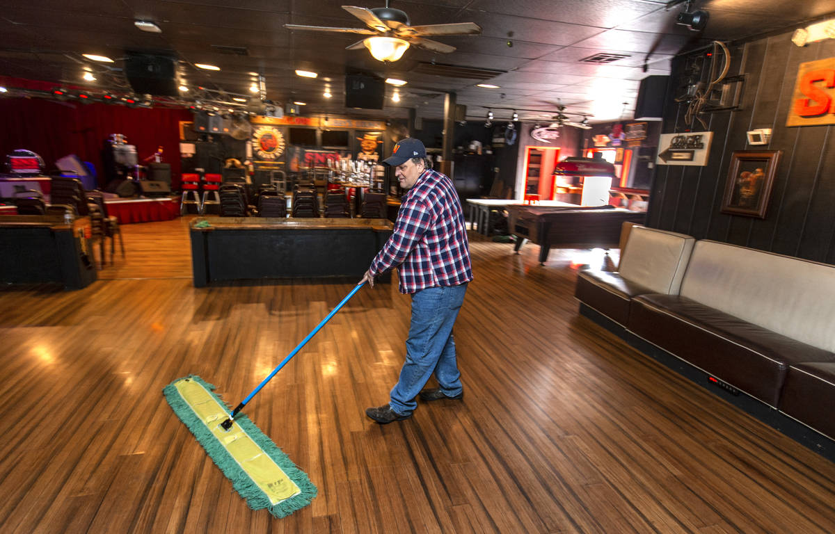 Saddle N Spurs Saloon owner Bobby Kingston continues to clean up his bar, closing for the next ...