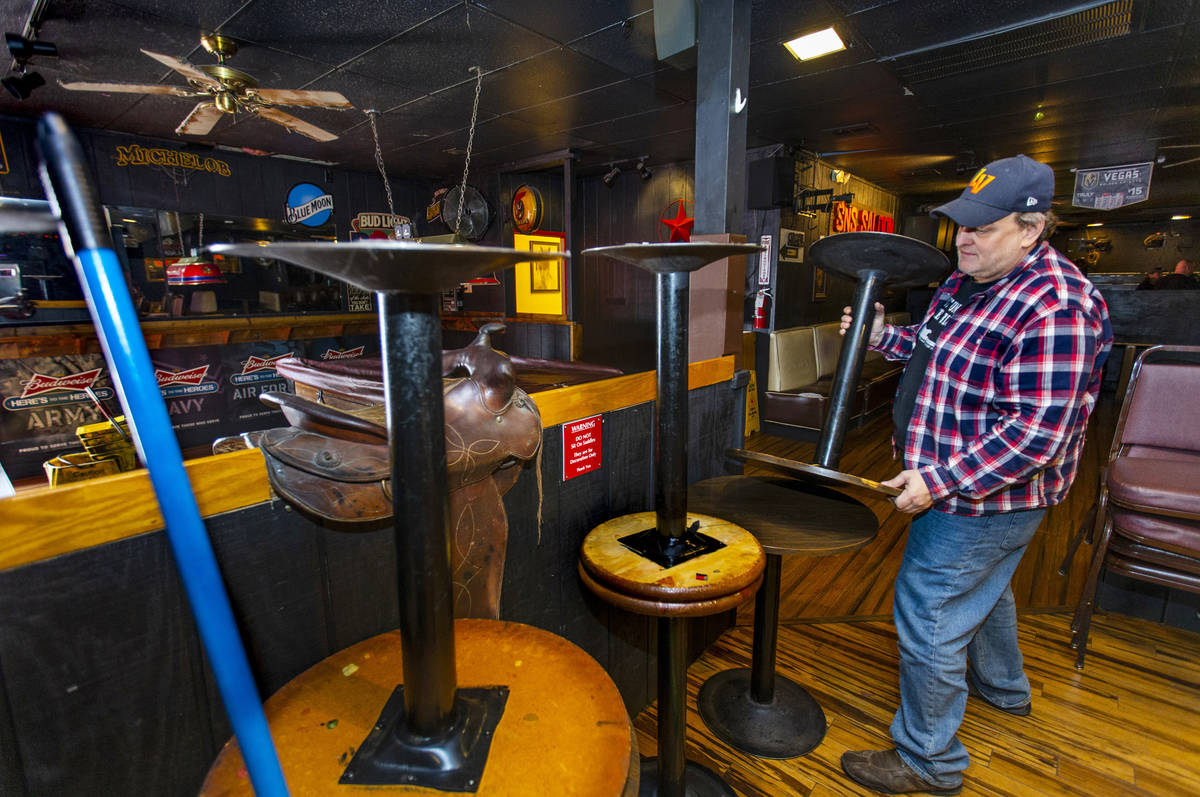 Saddle 'N' Spurs Saloon owner Bobby Kingston stacks tables in his bar, closing for the next 30 ...