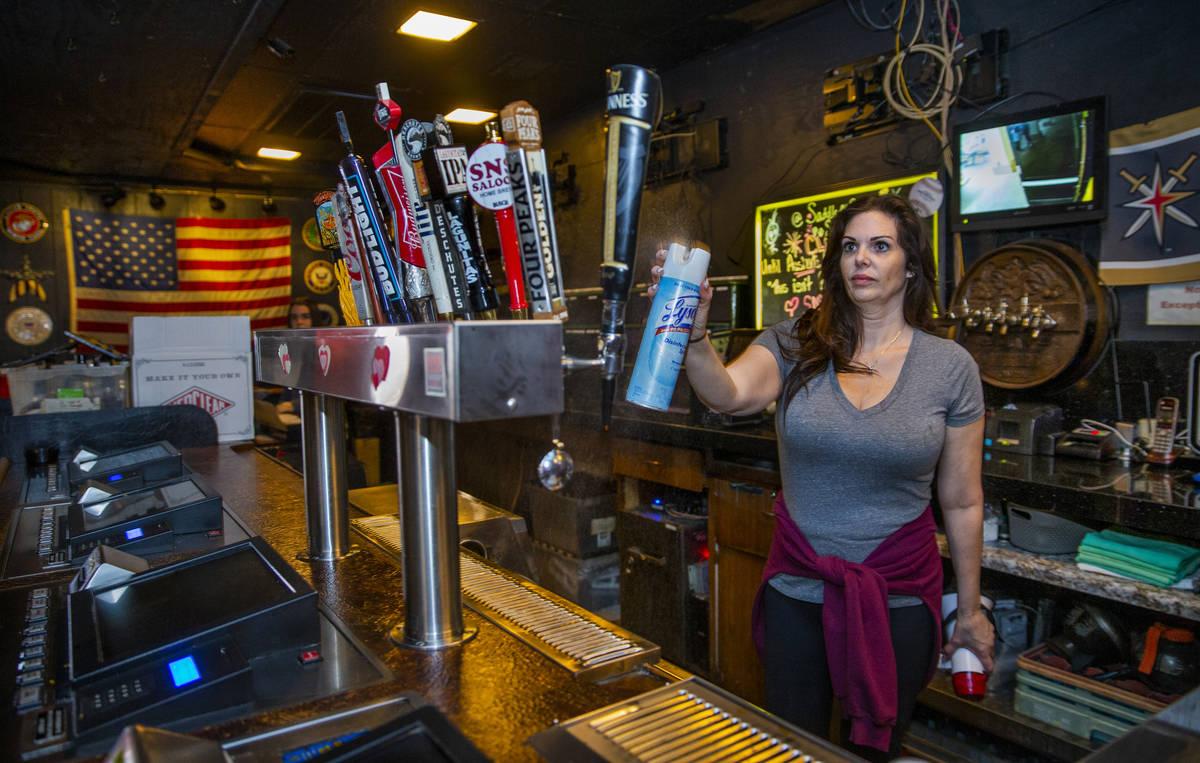 Saddle 'N' Spurs Saloon owner Melissa Kingston sanitizes bar taps as she and husband Bobby clo ...