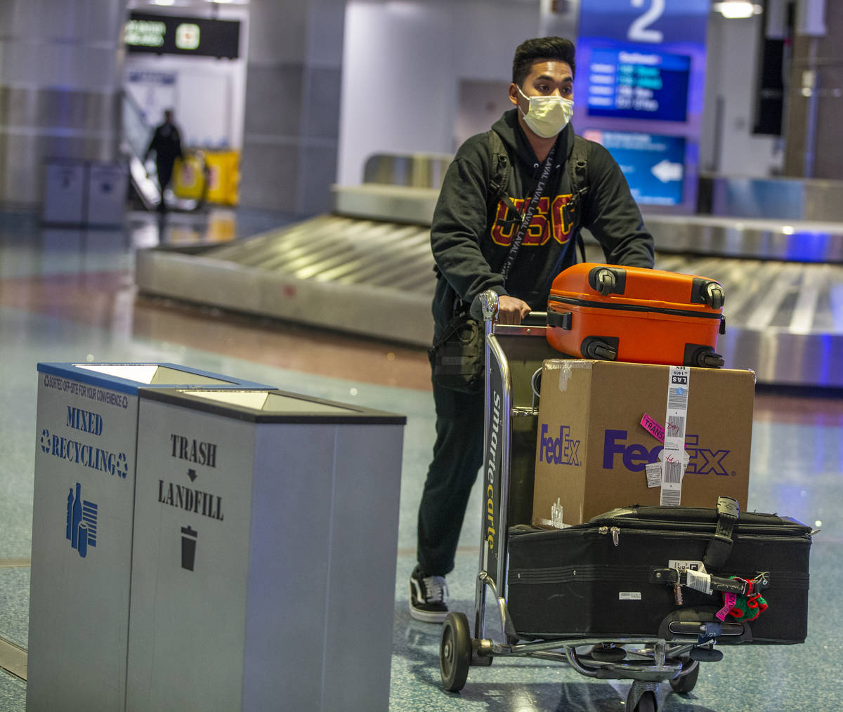 A masked passenger wheels his luggage from the baggage area in Terminal 1 at McCarran Internati ...