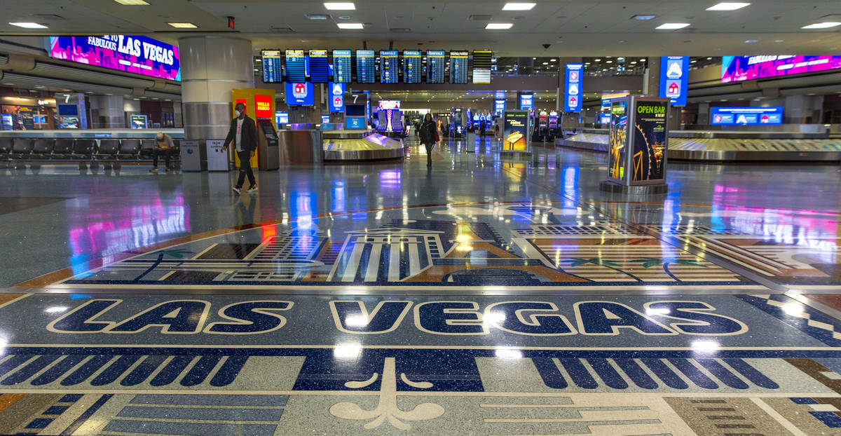 A masked passenger walks from the baggage area in Terminal 1 at McCarran International Airport, ...