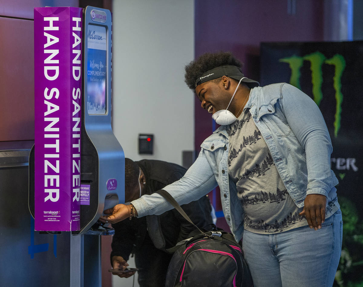 Masked passenger Daleonne Clark of Houston laughs with a friend while getting some hand sanitiz ...