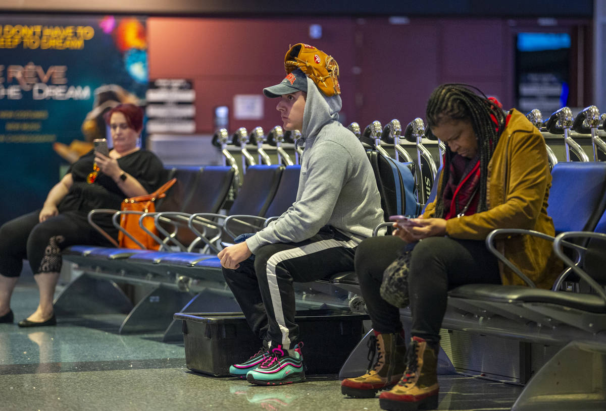 Passenger Montana Gomez wears his baseball glove on his head while waiting in the baggage area ...