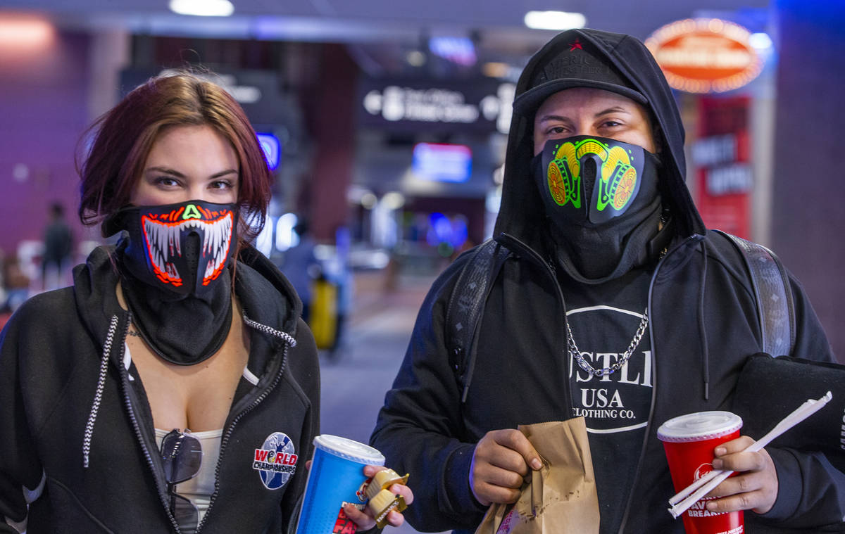 Passengers Sarah Lloyd and Johnny Calix of Orlando wear lighted masks in Terminal 1 while getti ...