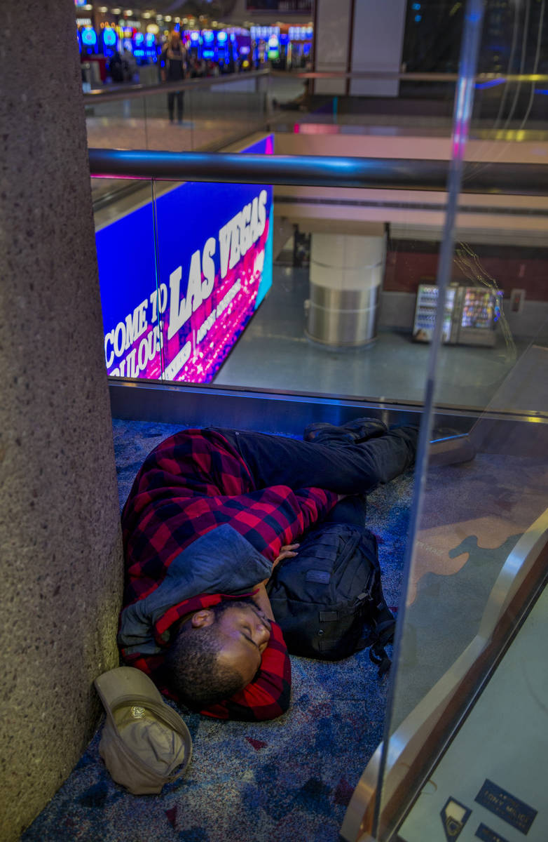A passenger naps in a corner within Terminal 1 at McCarran International Airport, now less crow ...