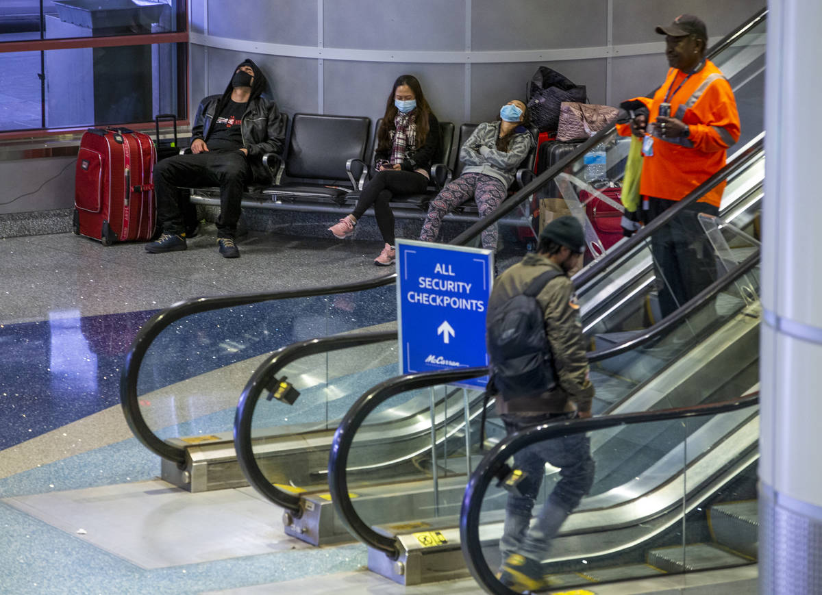 Passengers in masks kill some time awaiting their flights with others in the ticketing area of ...